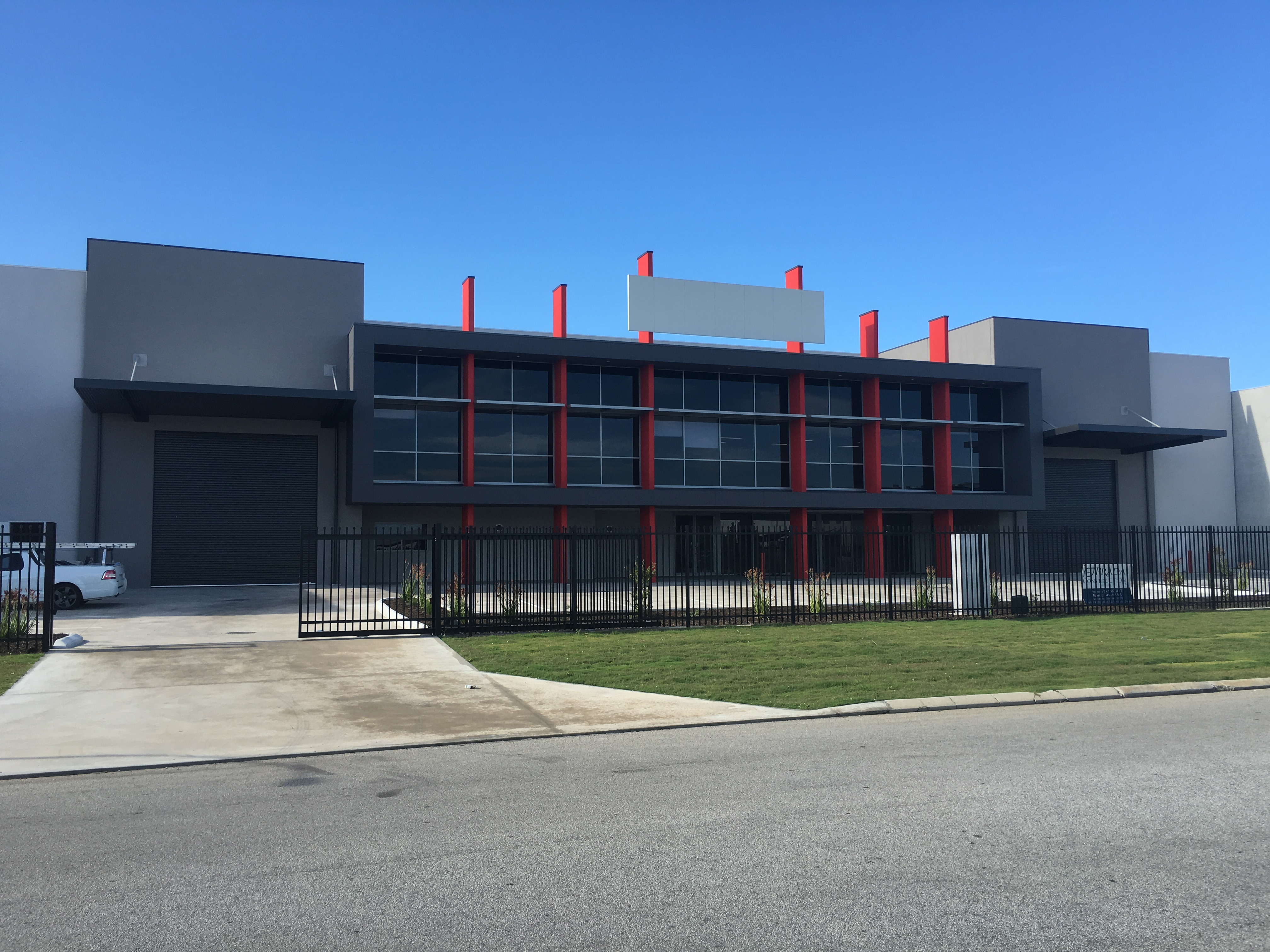 Exterior shot of large commercial office and warehouse complex, finished in dark grey with red accents