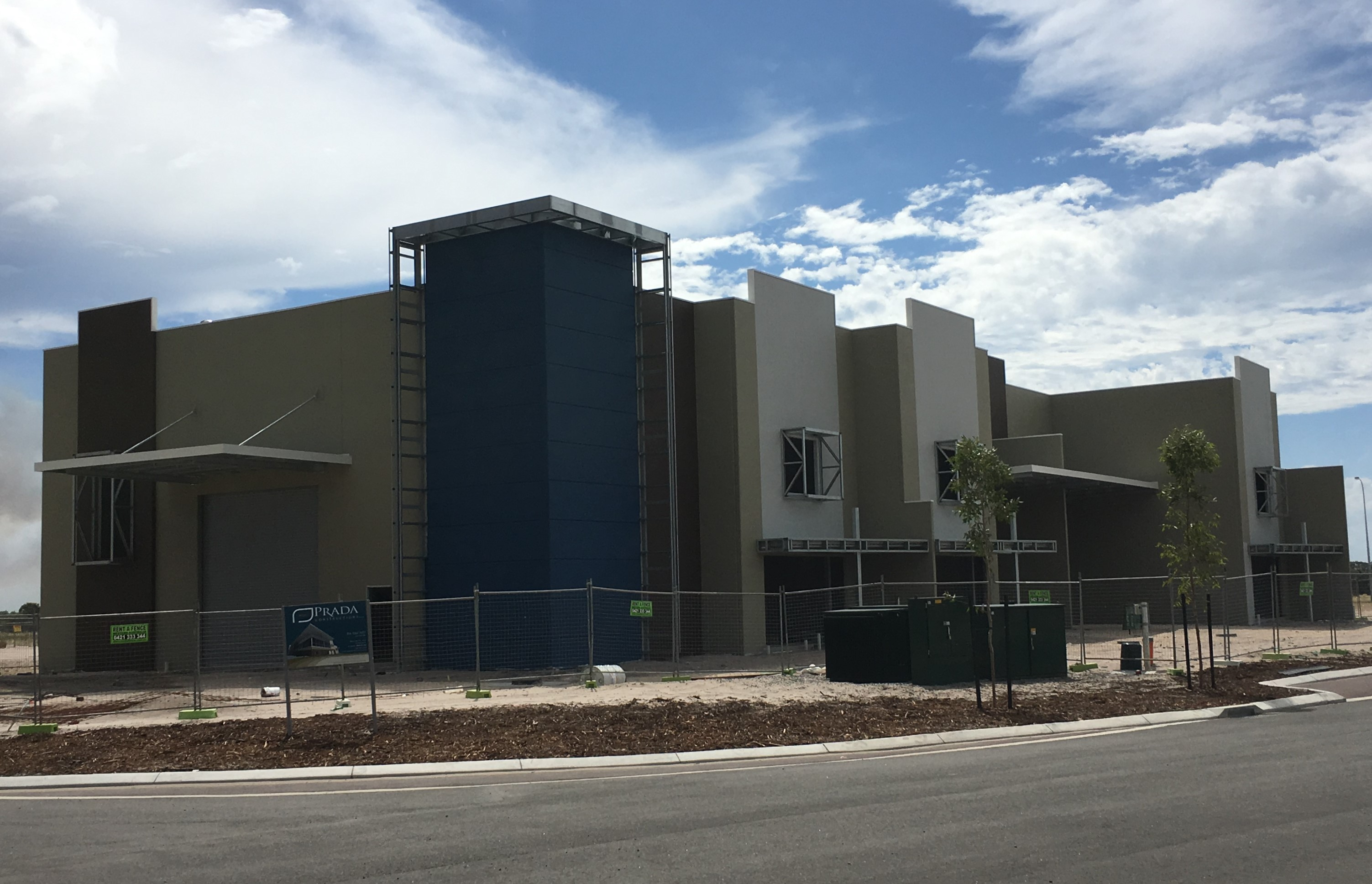 Exterior shot of large industrial warehouse/office painted in grey with blue accents