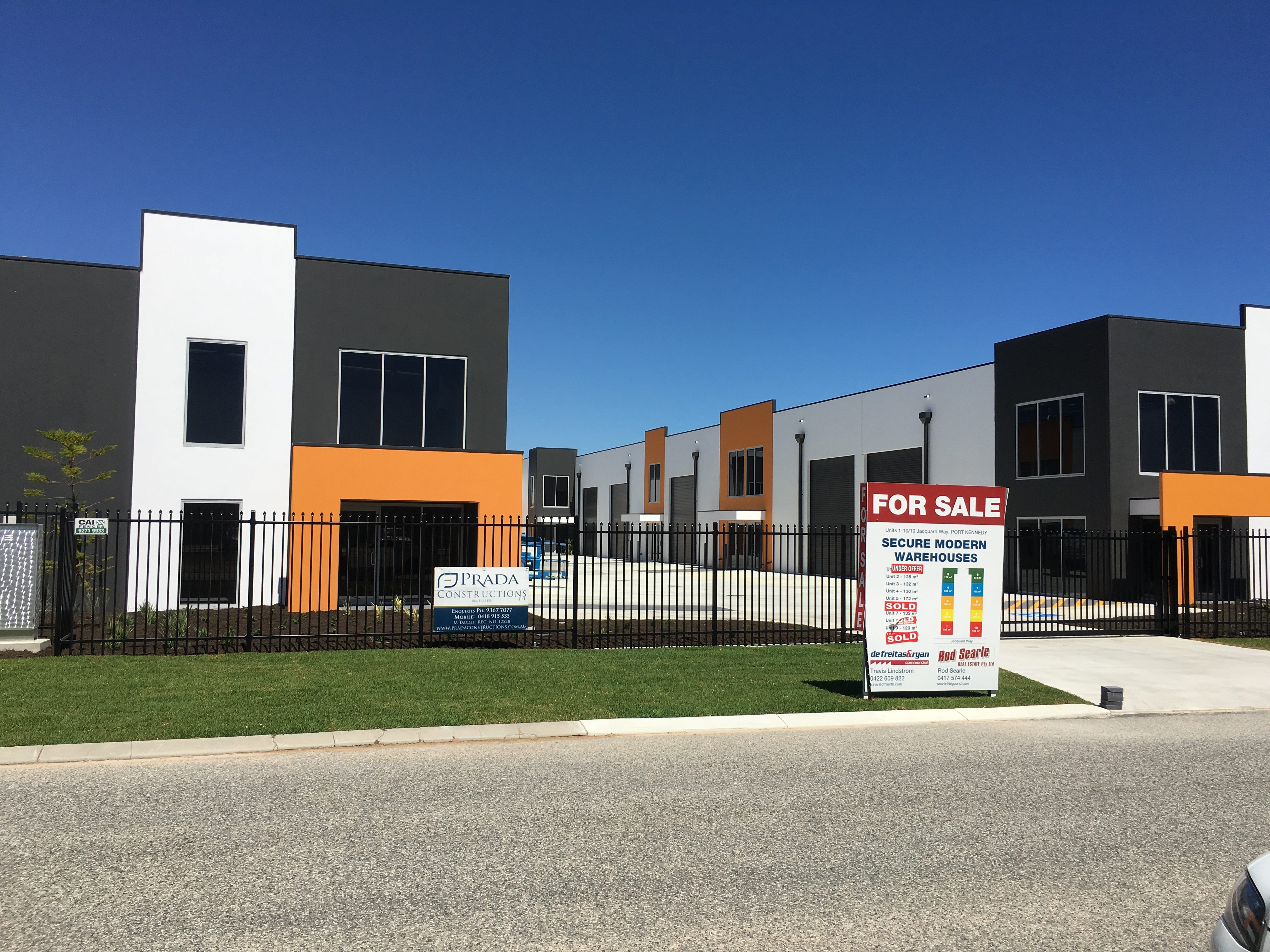 Exterior shot of fenced, modern warehouse units, finished in dark grey, orange and white