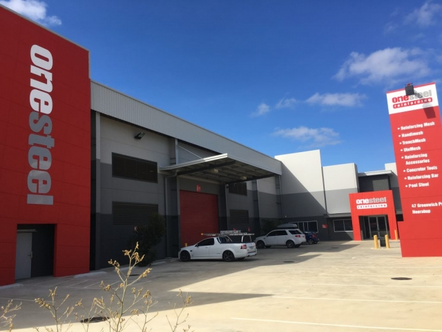 Exterior shot of OneSteel commercial premises, painted in grey tones and finished with red accents