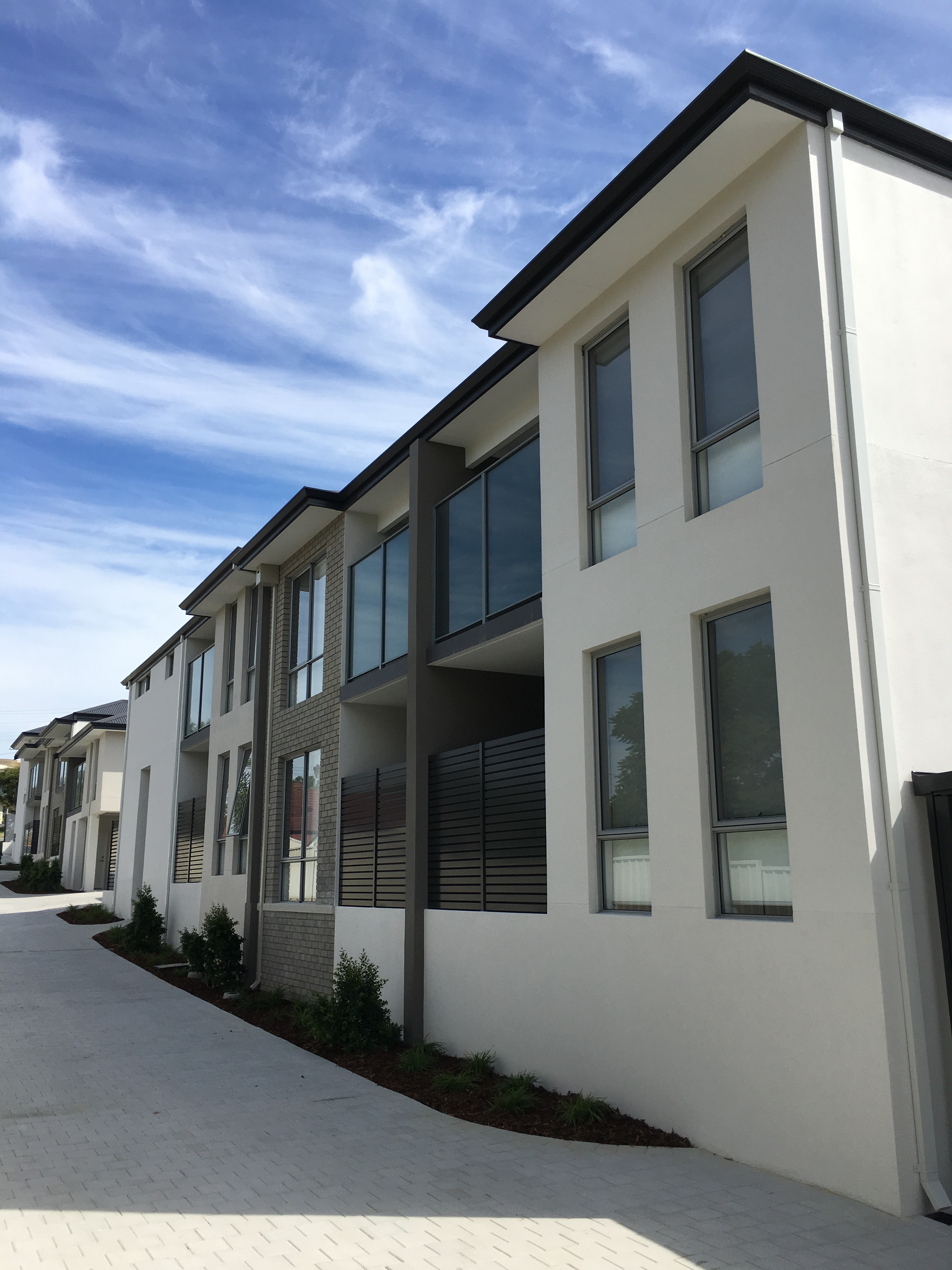 Exterior shot of large multi-unit complex painted in light grey and finished with dark grey and brick accents