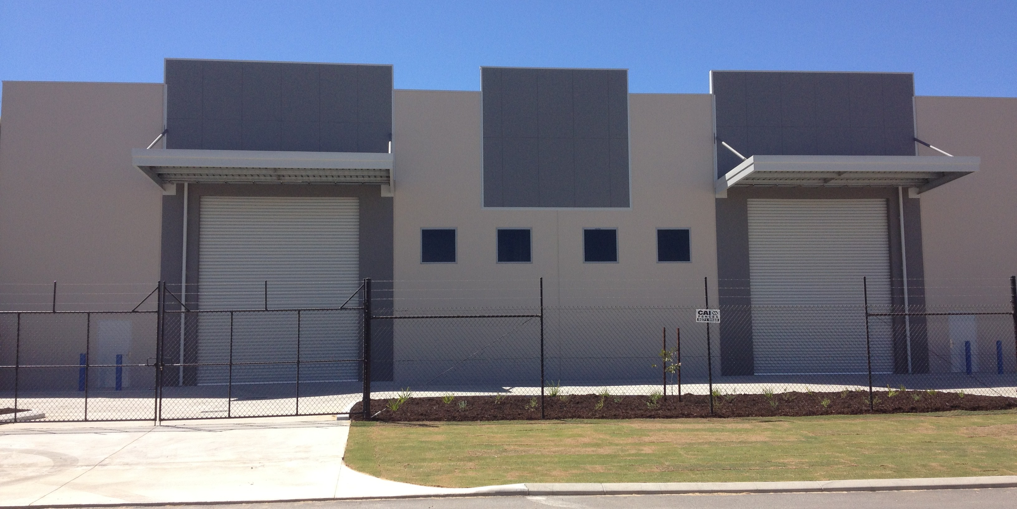 Exterior of large fenced commercial warehouse, painted in light grey with dark grey accents