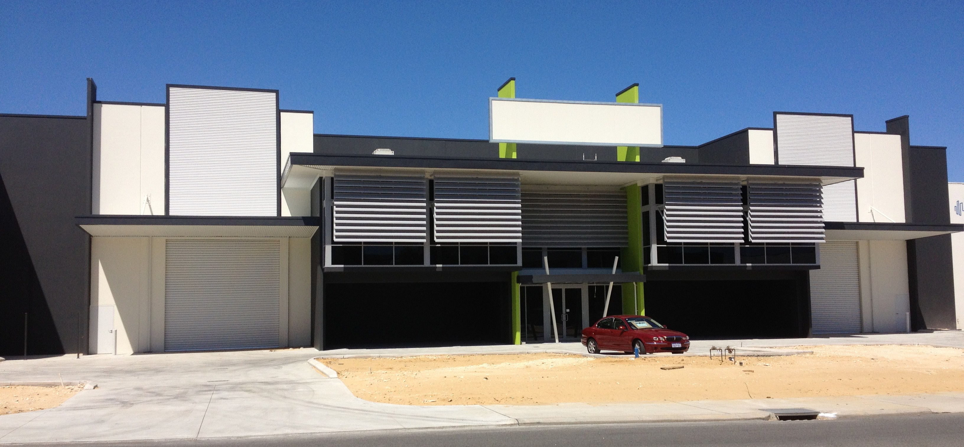 Exterior of large commercial warehouse units, painted in dark grey with lime accents.