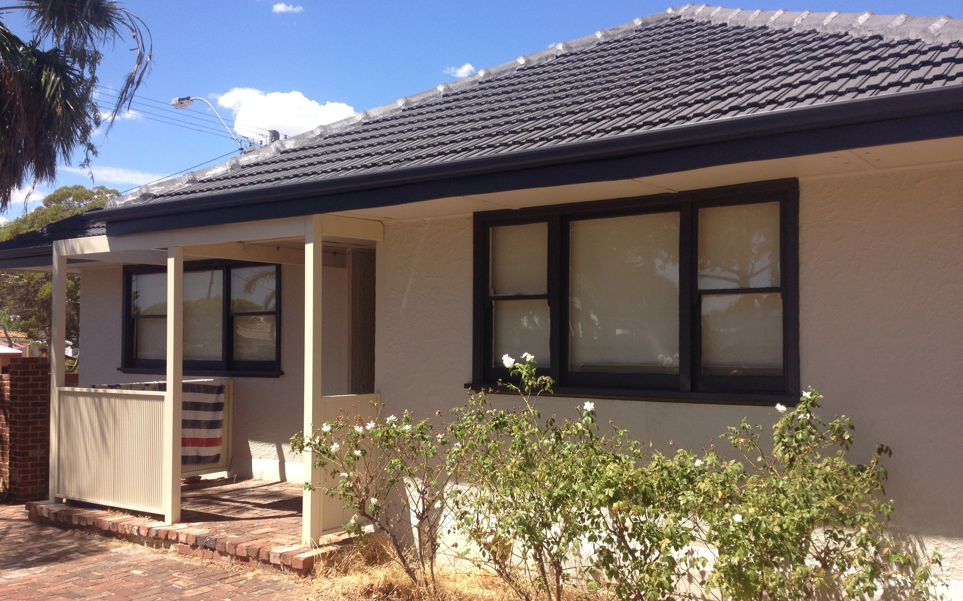 Exterior shot of older residential home painted in cream with dark grey window trims and roof