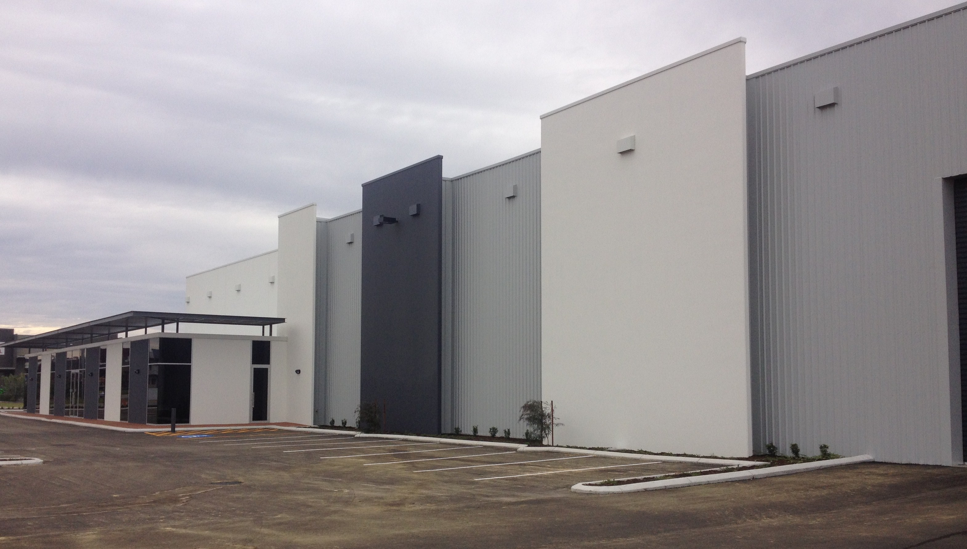 Exterior of large scale warehouse unit, painted in shades of grey