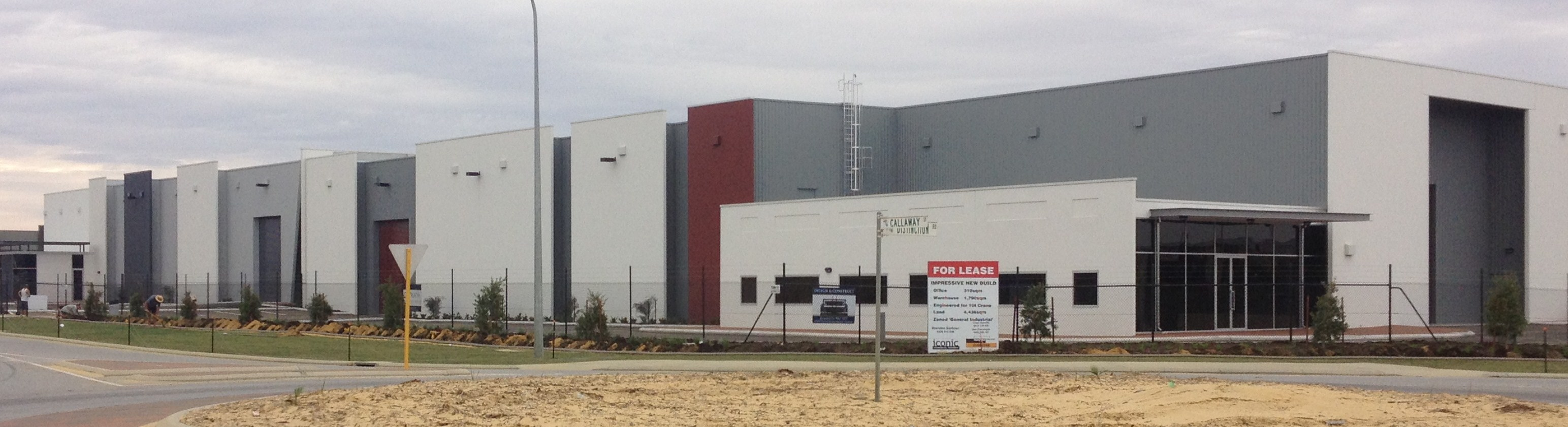 Exterior of large commercial multi-unit warehouse complex, finished in white, grey and red