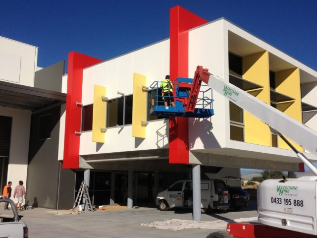 Exterior shot of man painting a commercial building in vibrant colours