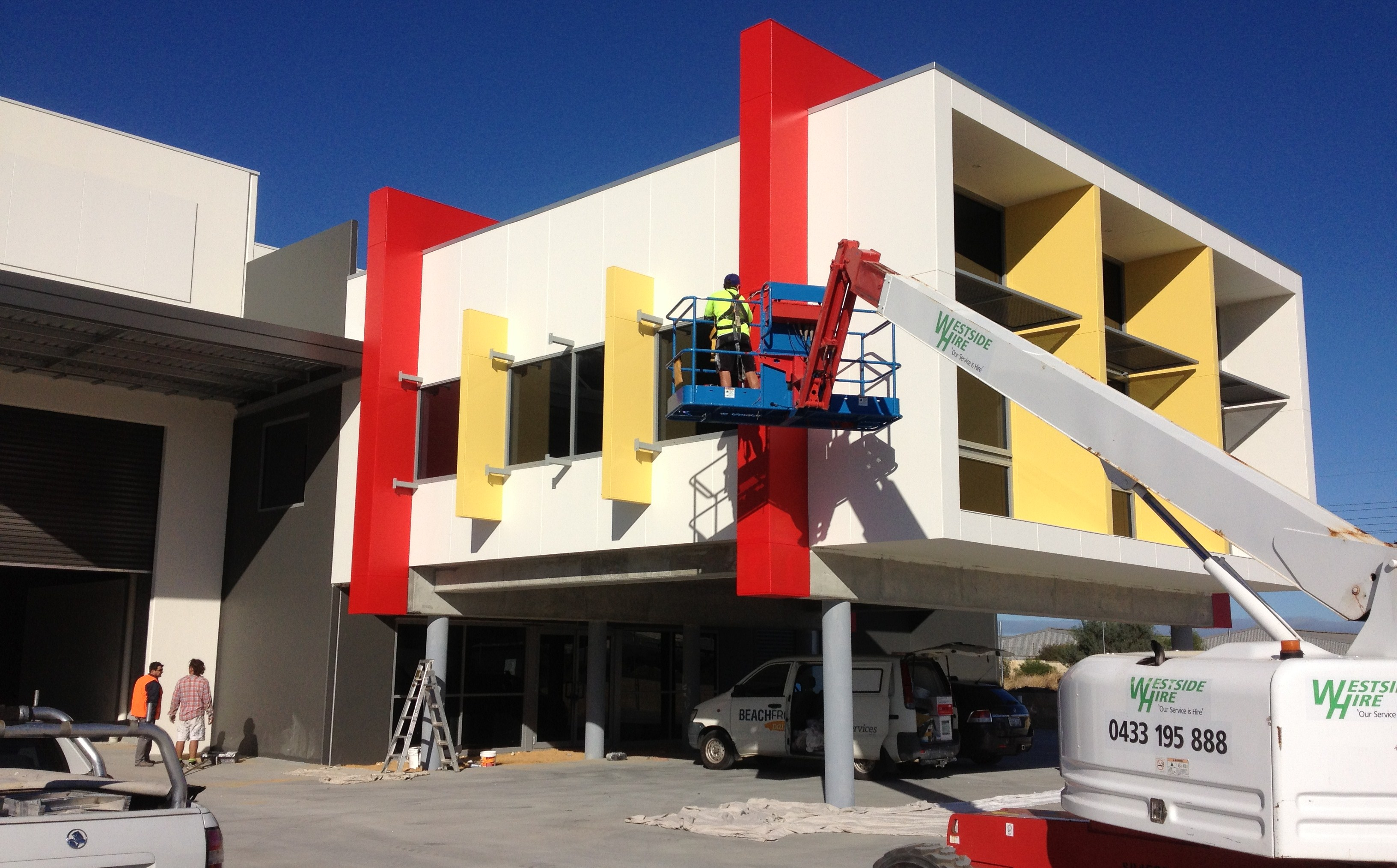 f37f641c6d Exterior shot of man painting a commercial building in vibrant colours