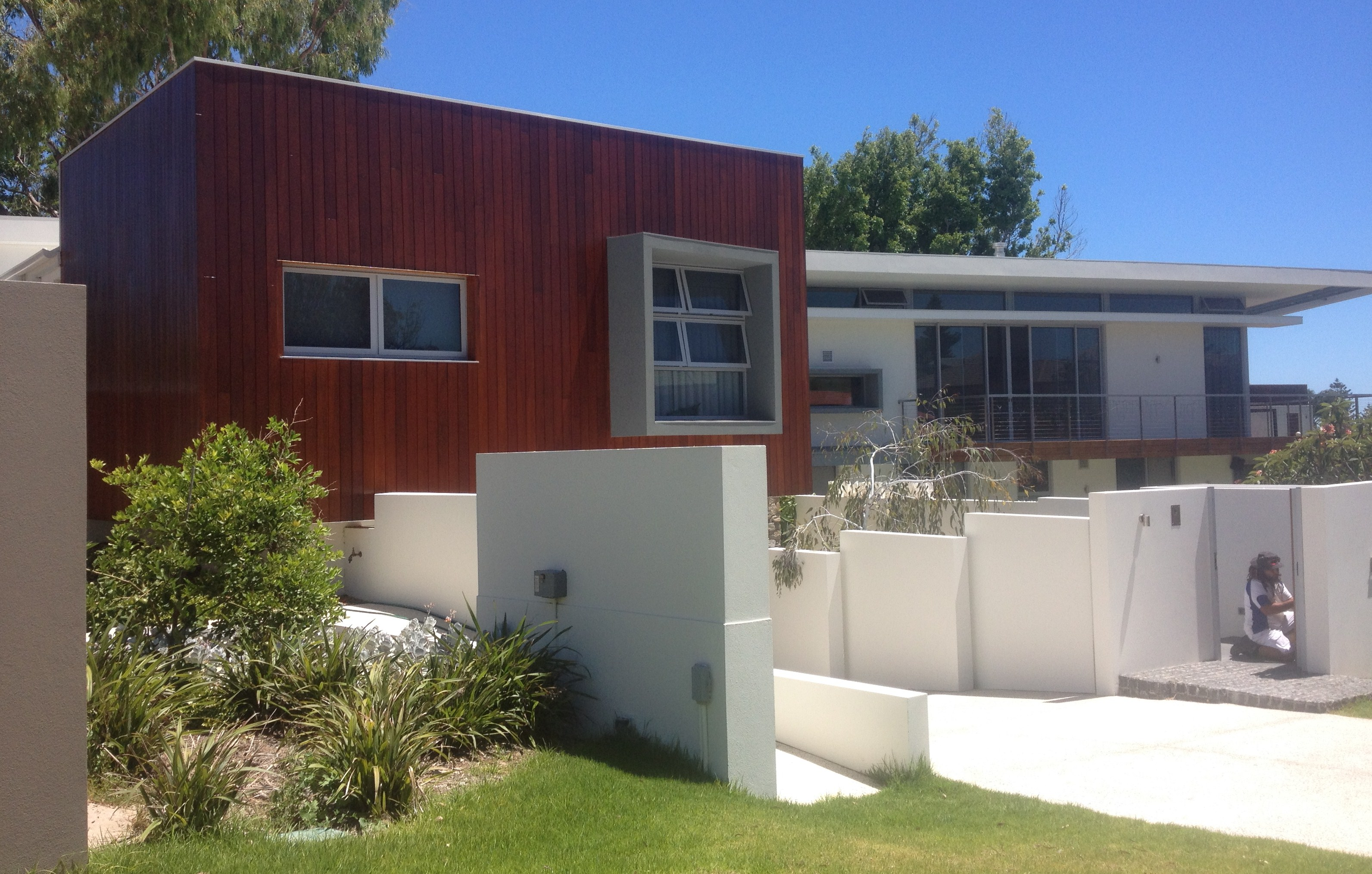 Large modern residential home finished with wood and painted in dark brown stain and white wash