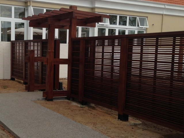 High residential fence and pergola painted in brown stain