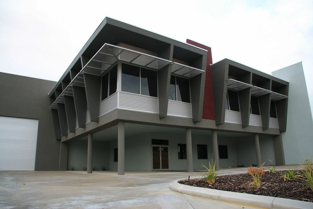 Exterior paint job of large commercial warehouse office, finished in grey with red accents